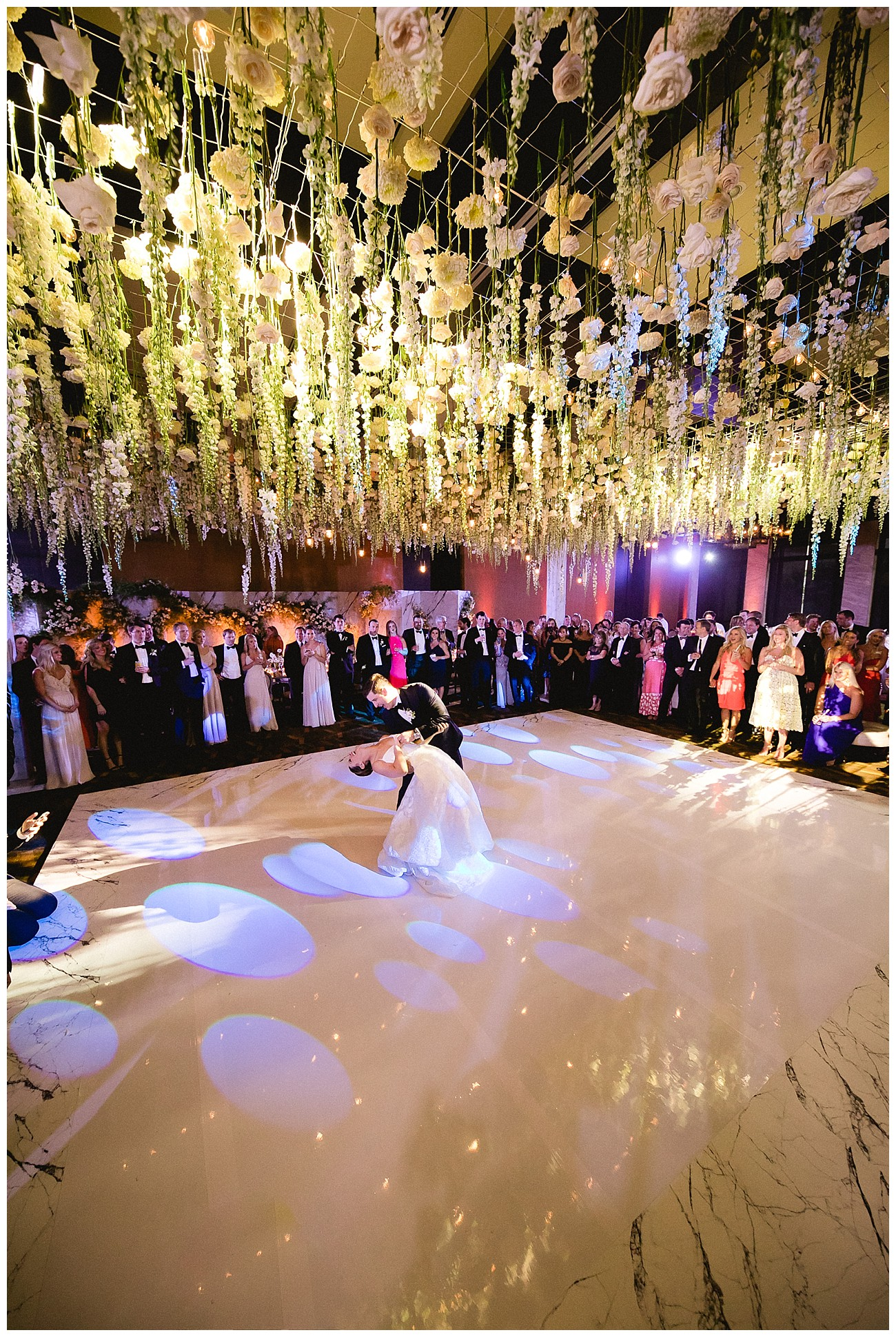 bride and groom doing their first dance under a stunning floral arrangement at white floral theme for a wedding at JW Marriott San Jose del Cabo