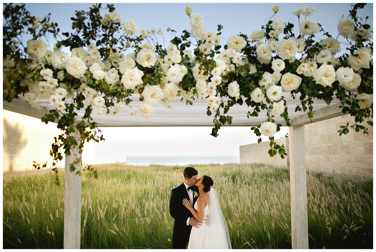 under an arbor of white roses at wedding at JW Marriott San Jose del Cabo