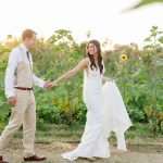 hand in hand during their white wedding at Flora Farms